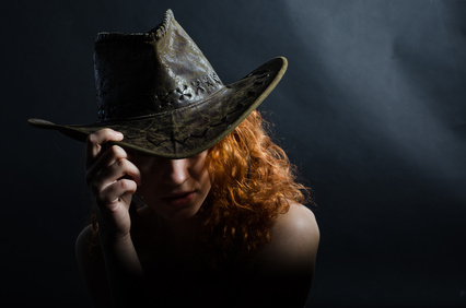 Girl in cowboy hat sturdio shot from the back on black background.